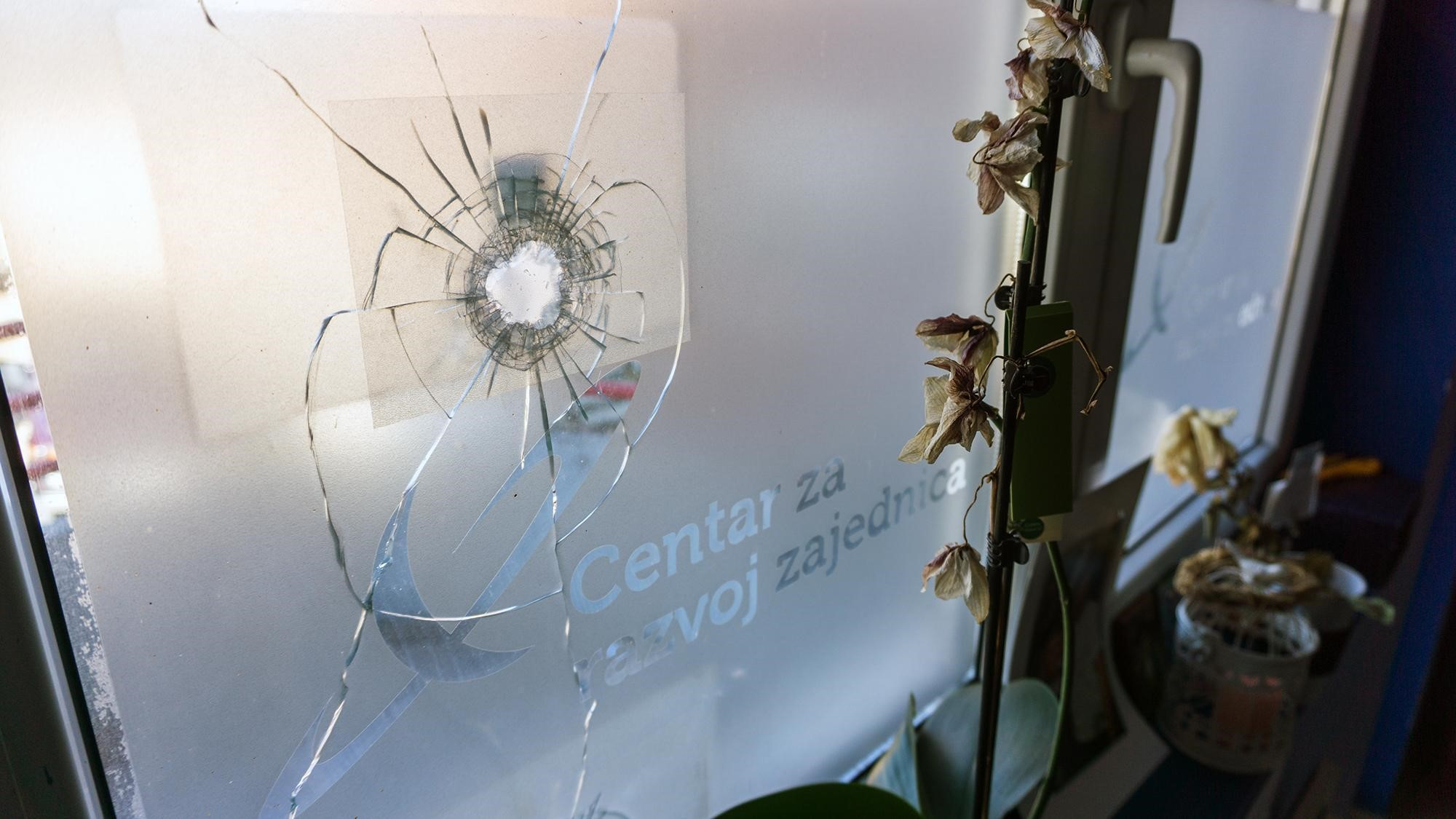 A bullet hole is seen in the window at the headquarters of independent media outlet Kossev in Mitrovica. Photo: Stefan Milivojevic